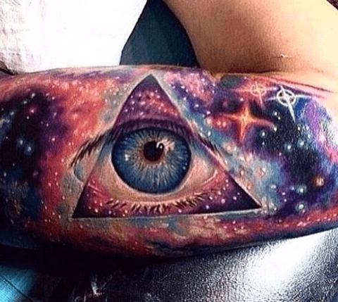 tattoo en el brazo, ojo realista en las estrellas