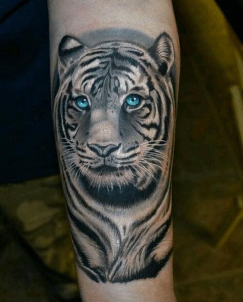 tattoo en la pierna de tigre con los ojos azules