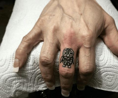 tattoo de búho en el dedo corazón