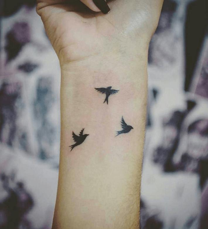 tattoo pájaros volando en la muñeca