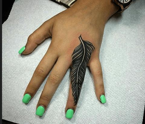 tattoo grande de pluma en el dedo
